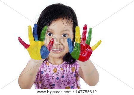 Portrait of a cute little girl showing her hands painted in colorful isolated on white background