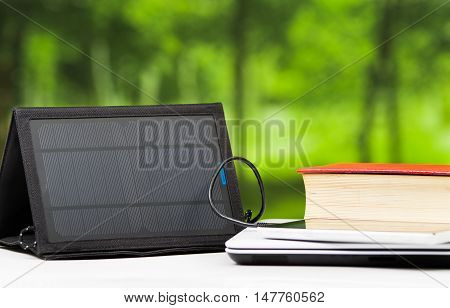 Portable solar charger sitting on white desk surface connected to tablet, modern technology concept, window garden background.