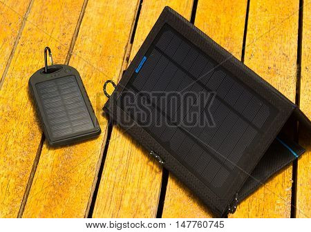 Two portable solar chargers sitting on wooden surface, modern green technology concept.