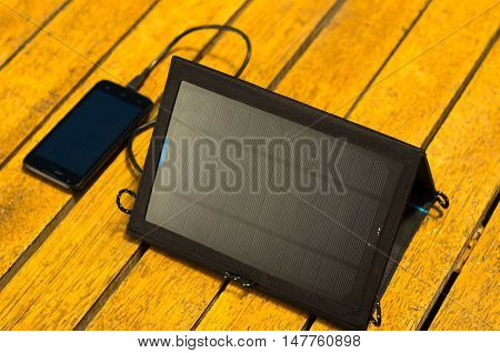 Portable solar charger sitting on wooden surface next to mobile phone, as seen from above, modern green technology concept.