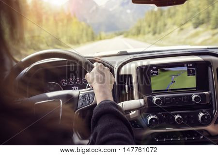 Woman holding the steering wheel driving a car on a rural road through the mountains