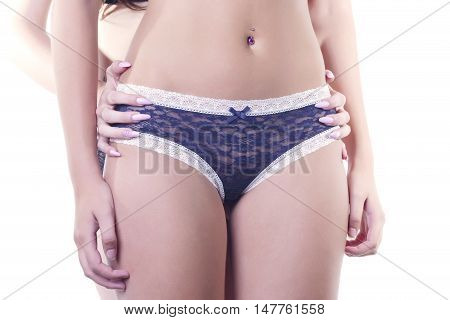 One girl on blue panties with her hands down while another girl holds her on waist. In studio over a white background isolated.