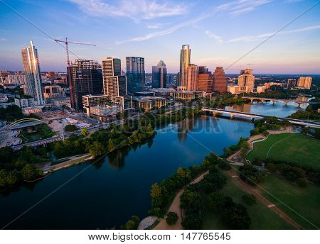 Aerial Over Austin Texas Summertime Golden Hour with Sun hitting the Skyline Cityscape at sunset with Colorado River or Town Lake reflecting bridges and the Capital City