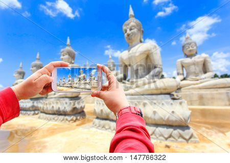 Smartphone photographing buddha statue and blue sky Nakhon Si Thammarat Province Thailand