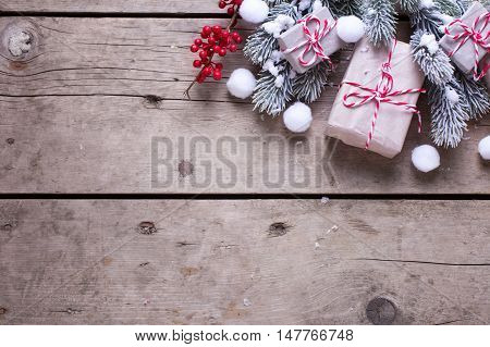 Wrapped christmas presents fur tree branches red berries on aged wooden background. Selectife focus. Top view. Place for text.