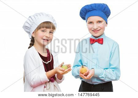 Children holding christmas cake pop dessert in shape of new year tree balls. Isolated over white background. Copy space.