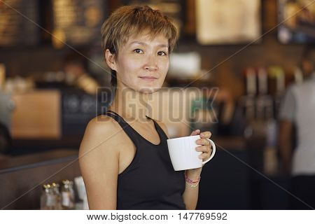 young beauty smiling and holding mug in coffee shop