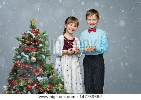 Beautiful little boy and girl standing near christmas tree, holding party dessert. Over snow backgroud. Copy space