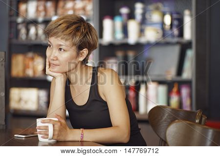 young Chinese woman looking outside holding mug