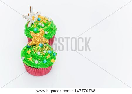 Christmas tree cupcakes over white background. Copy space.