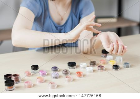Make up artist testing eyeshadow colors. Woman stylist trying cosmetics color on her hand. Professional coloring, visagiste, beauty concept, swatches
