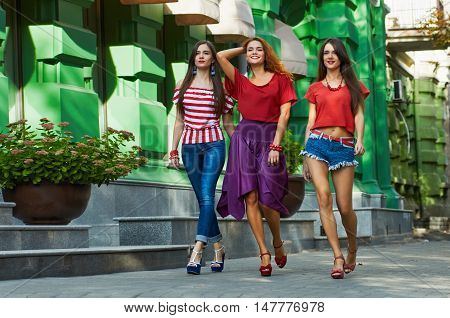 Young pretty girls best friends, sisters-triplets smiling and having fun, walking at the city. Wearing stylish outerwear. Bright make up. Positive emotions. full length