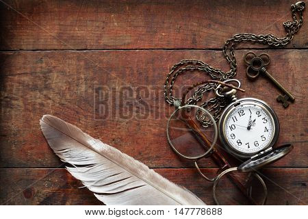 Old spectacles near pocket watch and feather on wooden background