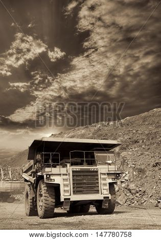 Heavy dump truck transporting iron ore from the opencast on sunset - black and white image