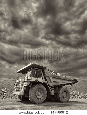 Heavy mining truck driving through the iron ore opencast with dramatic sky on the background - black and white image