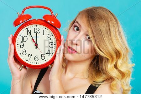 Management time concept. Blonde girl serious pensive face expression with alarm clock on blue.