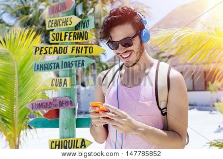 Young traveler in Holbox island (Mexico) with a sign pointing nearby towns and local food.