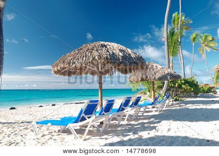 Beautiful caribbean beach with chaise lounge in Dominican Republic