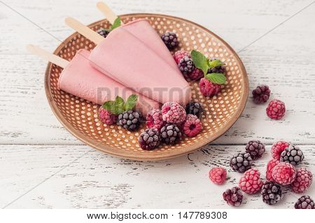 Raspberry popsicle with berries on wooden background, popsicle top view