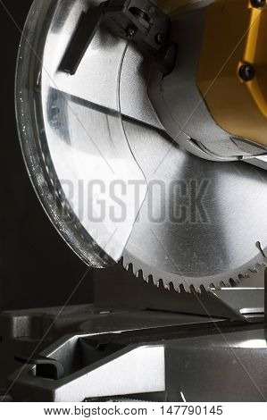 miter saw. Cutting disk on black background.