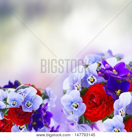 Posy of violets, pansies and ranunculus with copy space on gray bokeh background