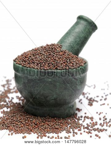 Organic Brown Mustard (Brassica juncea) on marble pestle and over white background.