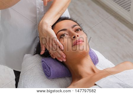 Massagist with woman patient in aroma spa wellness center. Professional face lifting massage to beautiful girl in cosmetology cabinet or beauty parlor.