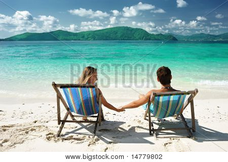 Couple on a tropical beach in chaise lounge