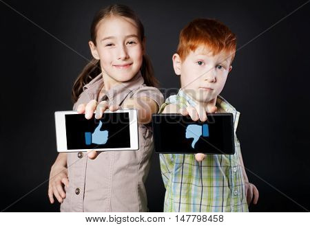 Portrait of happy, smiling girl and unhappy boy, children show mobile phone with with thumb up down symbols at black background. Positive and negative facial expression, emotions. Social networks