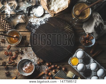 Christmas holiday cooking and baking ingredients. Cookie molds, spices, flour, eggs, cocoa powder, sugar, honey, nuts on rustic wooden background with dark wood board in center. Top view, copy space