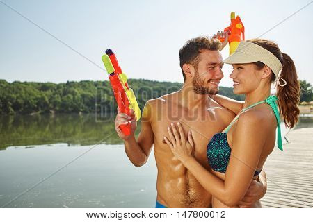 Happy couple in love at a lake with squirt guns hugging each other