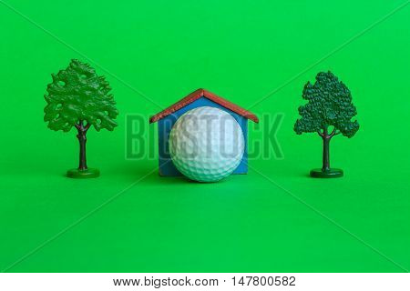 a house with a golf ball surrounded by trees and greenery is the symbol of the presence of a golf -club