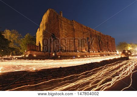 candle light trail of Buddhism Ceremony at temple ruin at dusk on Asalha Puja day