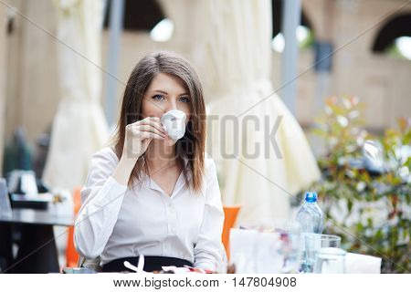 beautiful brunette young girl in outdoor cafe
