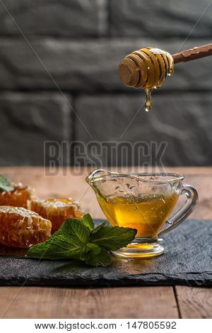 Honey dripping from a wooden honey dipper in sauceboat on dark background
