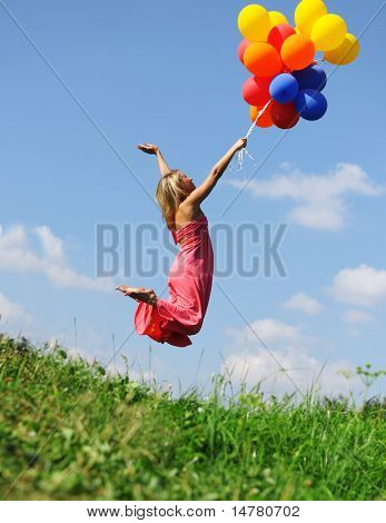 Girl jumping with balloons trying to fly