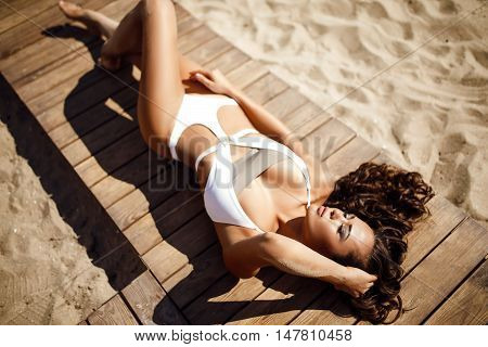 Portrait of attractive sensual woman in bikini with long wavy hair in wind with eyes closed posing on wooden path on beach