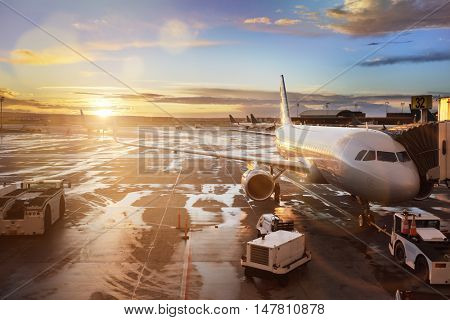 Airplane being preparing for takeoff at terminal gate in international airport at sunrise