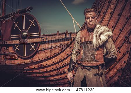 Viking warrior with axes standing near Drakkar on the seashore.