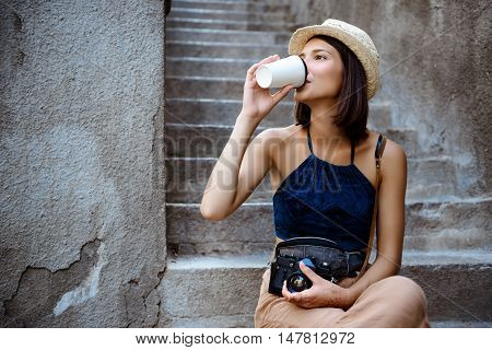 Young beautiful brunette female photographer in hat drinking coffee, sitting at stairs.
