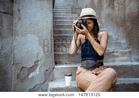 Young beautiful brunette girl in hat smiling, taking pictures, sitting at stairs.