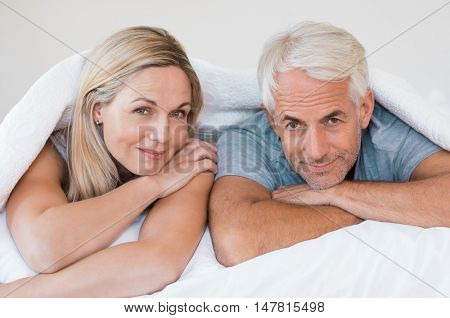 Senior romantic couple under a white duvet in the bed. Happy mature couple lying down in their bed and looking at camera. Retired man and smiling woman having fun lying on bed at home.