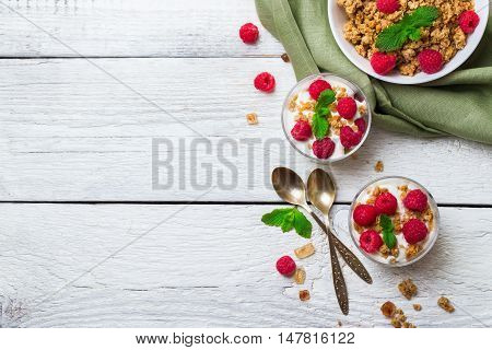 Breakfast, food, still life concept. Muesli granola berries homemade yogurt on a rustic white wooden table. Selective focus, top view flat lay overhead copy space