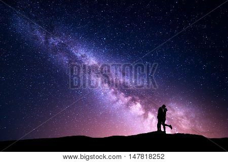 Milky Way. Night landscape with silhouettes of hugging and kissing man and woman on the mountain. Colorful sky with stars. Silhouette of lovers. Couple relationship. Milky way with people. Universe