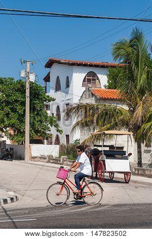 VARADERO CUBA - February 08 2008. Woman rides a bicycle on a street in Varadero town.