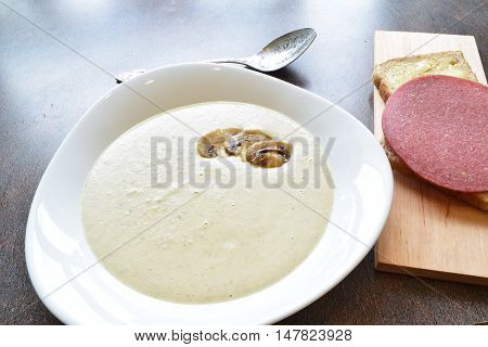 champignions cream soup with a piece of bread and wurst