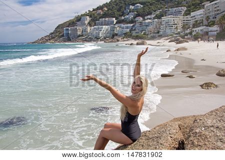 A beautiful beach babe sitting on a boulder at the beach showing us the ocean with an excited look on her face