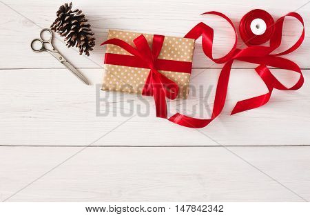 Creative diy hobby. Handmade tools for making christmas present, box in craft paper with red ribbon. Top view of white wooden table with copy space, decoration of gift.