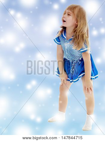 On a blue background with white blurry circles, like Christmas snowflakes. Cute little unkempt girl in a short blue dress. Girl looking to the side with his hands on his knees.