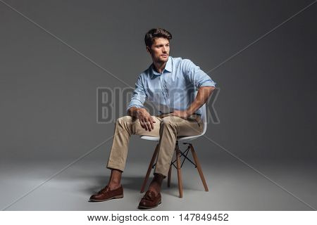 Pensive brunette man in blue shirt sitting on the chair and looking away over grey background